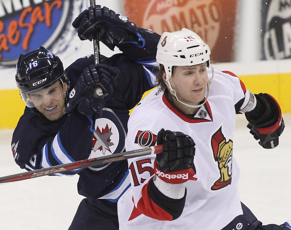 Description of . WINNIPEG, CANADA - JANUARY 19:  Andrew Ladd #16 of the Winnipeg Jets crashes into Zack Smith #15 of the Ottawa Senators during third period action on January 19, 2013 at the MTS Centre in Winnipeg, Manitoba, Canada. (Photo by Marianne Helm/Getty Images)