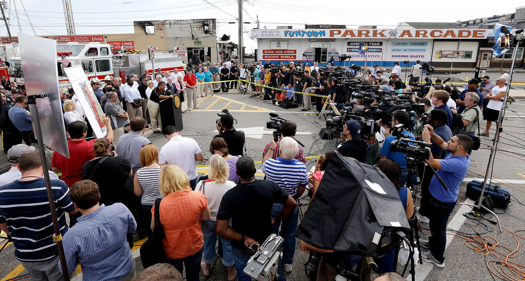 Description of . A crowd of journalists attend a news conference with New Jersey Gov. Chris Christie, center left, the morning after a massive fire burned a large portion of the Seaside Park boardwalk, Friday, Sept. 13, 2013, in Seaside Park, N.J. (AP Photo/Julio Cortez)