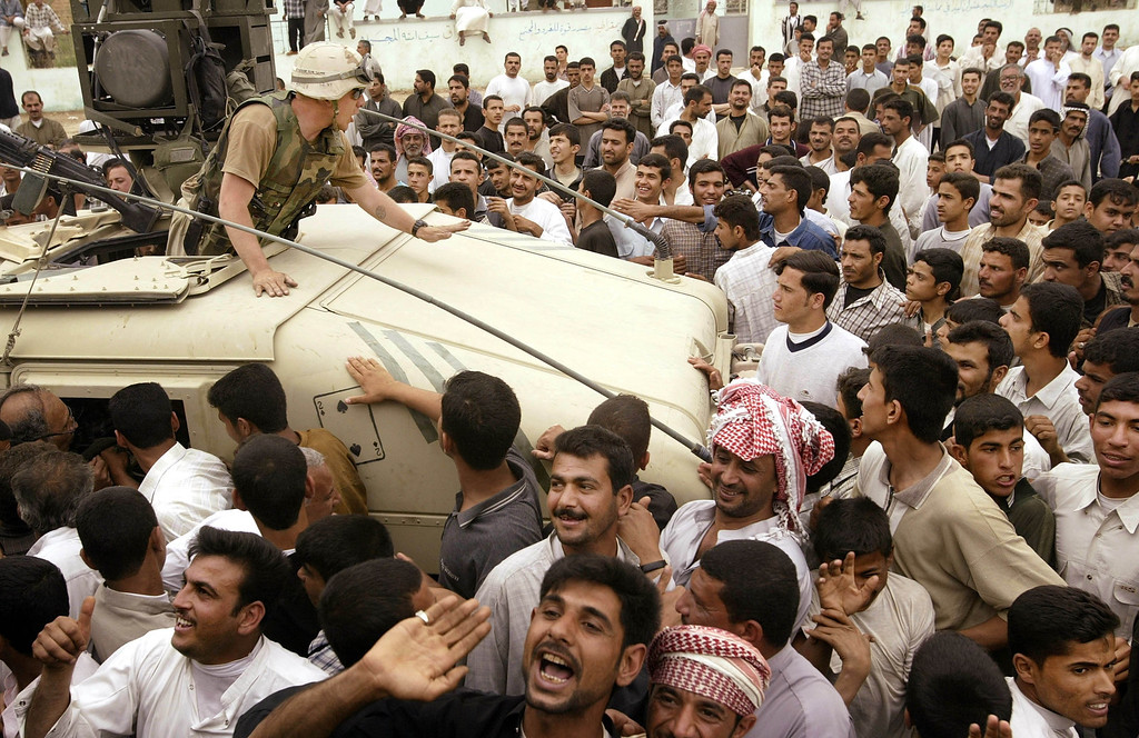 . Villagers celebrate the arrival of the U.S. Marines April 7, 2003 in Qal\'at Sukkar, Iraq. The 24th Marine Expeditionary Unit entered the town looking for weapons and to destroy pictures of Saddam Hussein. (Photo by Chris Hondros/Getty Images)