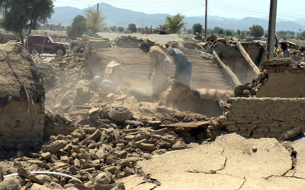 Description of . Pakistani earthquake survivors remove debris from their collapsed mud houses in the earthquake-devastated district of Awaran on September 25, 2013.  AFP PHOTO/Banaras KHAN/AFP/Getty Images