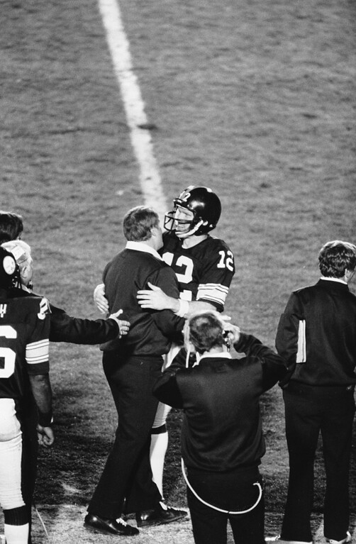 Description of . Pittsburgh Steelers quarterback Terry Bradshaw (12) embraces coach Chuck Noll on the sidelines shortly after Bradshaw threw touchdown pass in second half of Super Bowl XIV game Sunday in Rose Bowl stadium in Pasadena, Ca., on Jan. 20, 1980.  Bradshaw led the Steelers to a 31-19 win over the Los Angeles Rams.  It is the fourth Super Bowl win for the Steelers.  (AP Photo)
