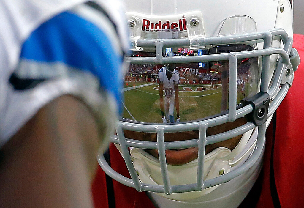 Description of . Detroit Lions wide receiver Calvin Johnson is reflected in the face mask of Arizona Cardinals defensive back Patrick Peterson during the second half of a NFL football game, Sunday, Sept. 15, 2013, in Glendale, Ariz. (AP Photo/Darryl Webb)