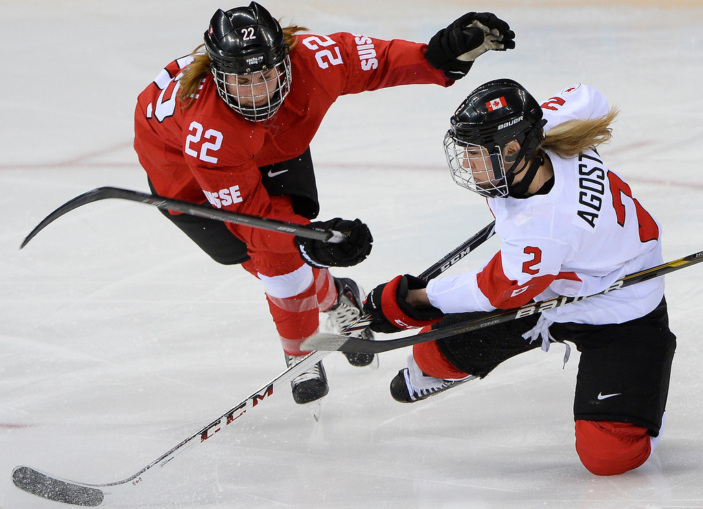 . Switzerland\'s Livia Altmann (L) vies with Canada\'s Meghan Agosta-Marciano during the Women\'s Ice Hockey semifinal match Canada vs Switzerland at the Shayba Arena during the Sochi Winter Olympics on February 17, 2014. Canada won 3-1. JONATHAN NACKSTRAND/AFP/Getty Images