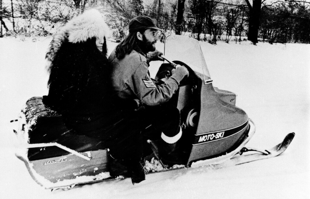 Description of . John Lennon, right, and his wife, Yoko Ono, take their first ride on a snowmobile on a farm owned by rock singer Ronnie Hawkins at Mississauga, Ontario, Canada, Dec. 18, 1969.  Lennon and Ono are staying on the farm during their peace crusade in Canada. (AP Photo)
