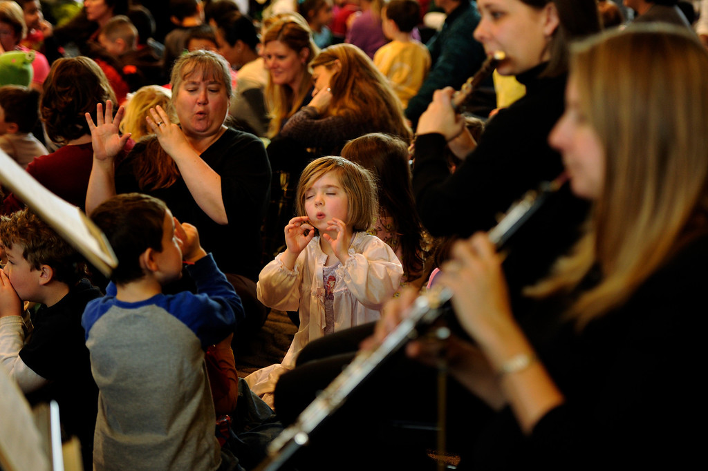 Description of . In her pajamas, Annie Wheeler, 5, of the Early Childhood Center plays an imaginary flute with members of the Junior Symphony Guild at the Inside the Orchestra for Tiny Tots performance at Temple Emanuel in Denver, Colorado on Thursday, February 9,  2012. Joe Amon, The Denver Post