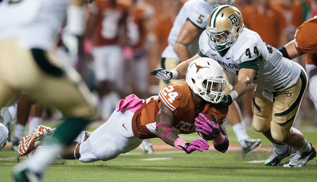Description of . AUSTIN, TX - OCTOBER 20:  Joe Bergeron #24 of the Texas Longhorns dives for extra yardage during the Big 12 Conference game against the Baylor University Bears on October 20, 2012 at Darrell K Royal-Texas Memorial Stadium in Austin, Texas.  (Photo by Cooper Neill/Getty Images)