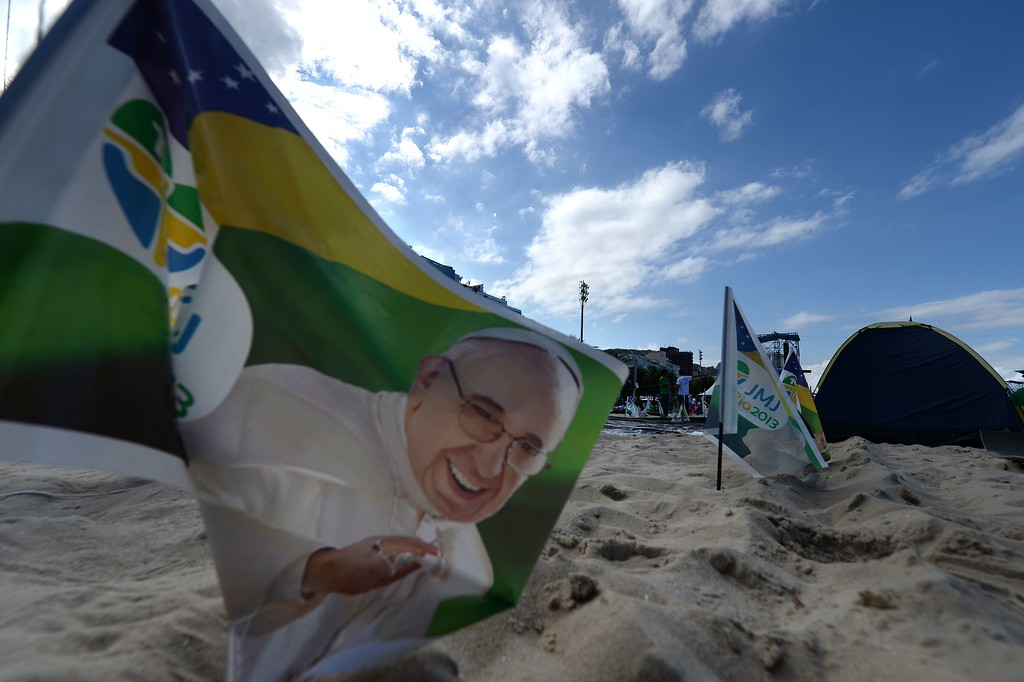 Description of . A flag with an image of Pope Francis is seen at Copacabana beach in Rio de Janeiro as hundreds of thousands of young Catholic pilgrims attending World Youth Day (WYD) start gathering for a prayer vigil with Pope Francis, on July 27, 2013. In a speech to Brazil's political, religious and civil society leaders earlier, Pope Francis said a