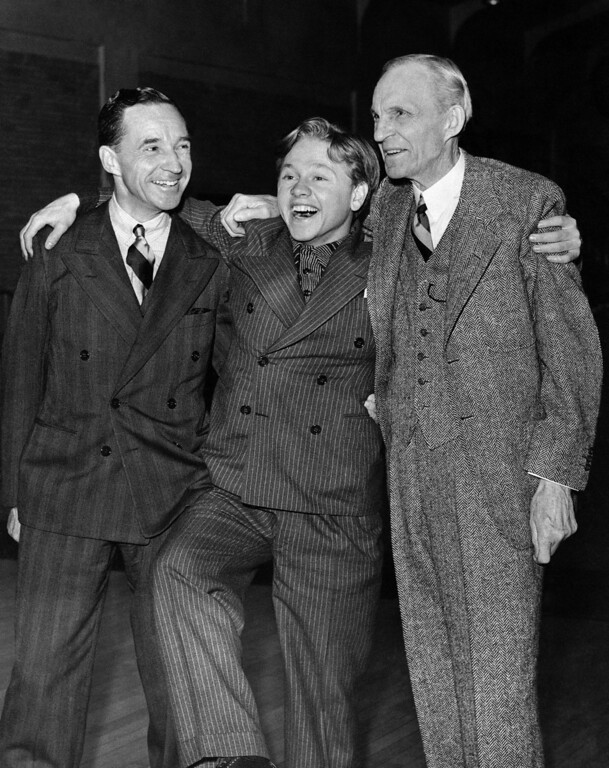 Description of . Movie actor Mickey Rooney with an armful of millionaires and dancing a jig in Detroit on Feb. 9, 1940. With him are Edsel and Henry Ford. Rooney has the title role in a Thomas Edison film which will have its world premiere Saturday at Port Huron, Mich. Henry Ford and Edison were close friends. Rooney was a guest of the Fords. (AP Photo)