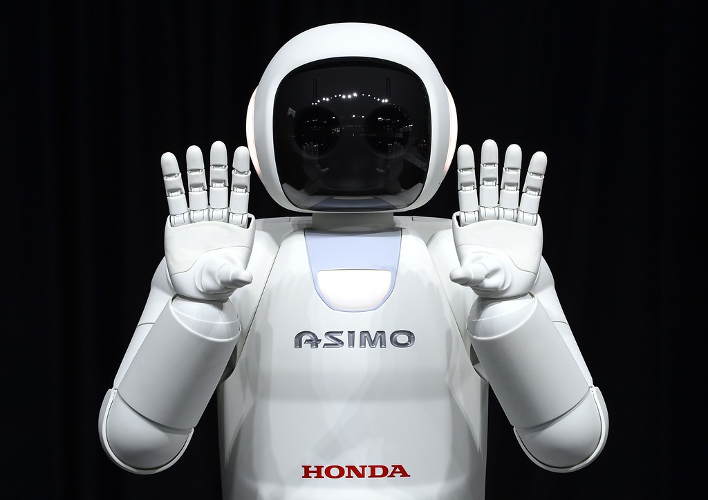 Description of . Honda North America shows off their new Asimo Robot along with their new Honda FIT to the media during the second press preview day at the 2014 New York International Auto Show  April 17, 2014  in New York at the Jacob Javits Center. AFP PHOTO / Timothy A. CLARY/AFP/Getty Images