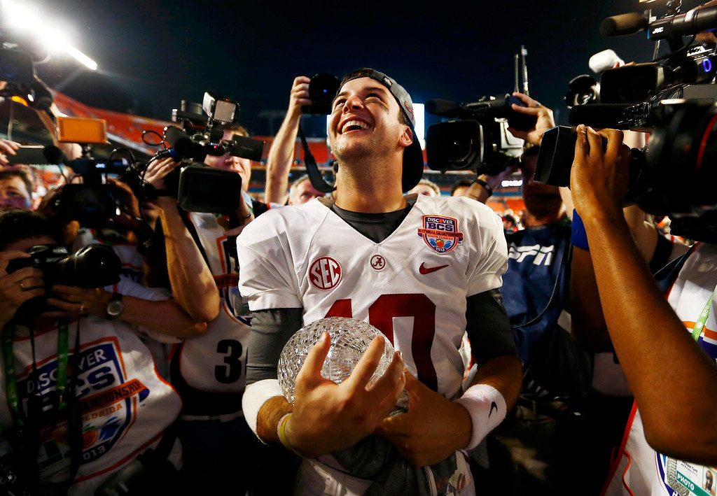 Description of . Alabama Crimson Tide quarterback AJ McCarron celebrates with the trophy after his team defeated the Notre Dame Fighting Irish in their NCAA BCS National Championship college football game in Miami, Florida, January 7, 2013.  REUTERS/Chris Keane