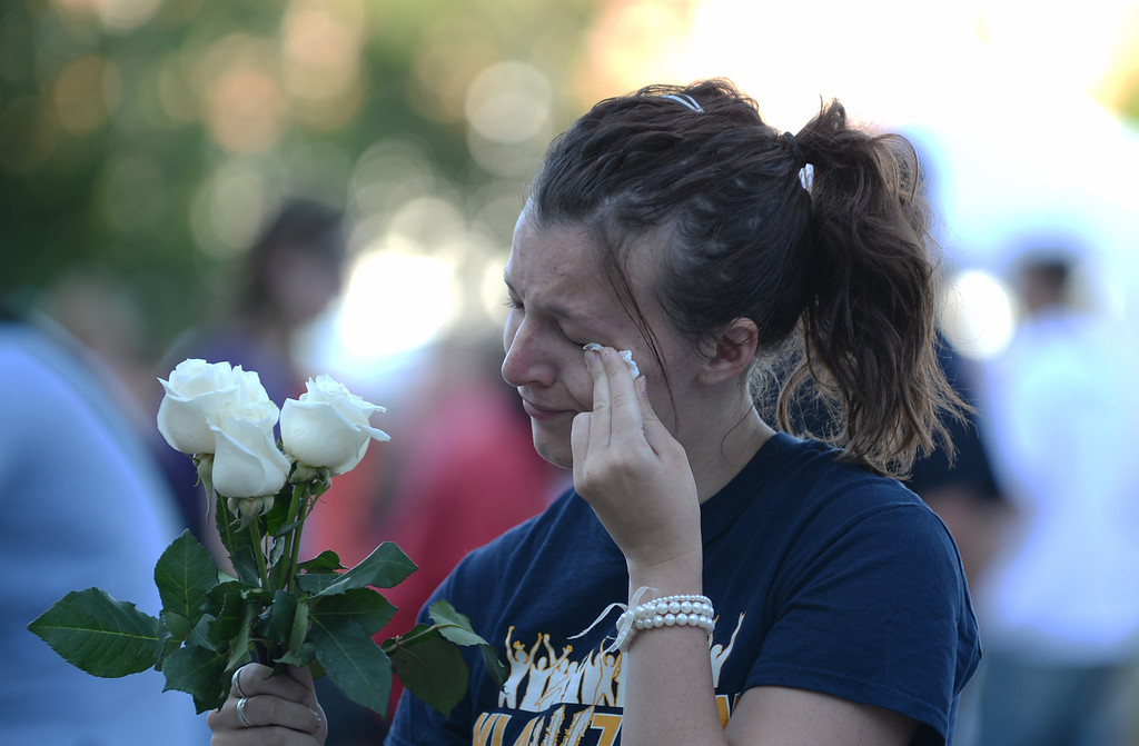 Description of . AURORA, CO. - July 20: Chelsea Willman, 20, wipes her tears during a day of remembrance at the Aurora Municipal Center. Aurora, Colorado. July 20, 2013. People gathered outside the Aurora Municipal Center to mark the first anniversary of the deaths of 12 people and the injury of at least 70 others in a mass shooting that forever changed an entire community. (Photo By Hyoung Chang/The Denver Post)