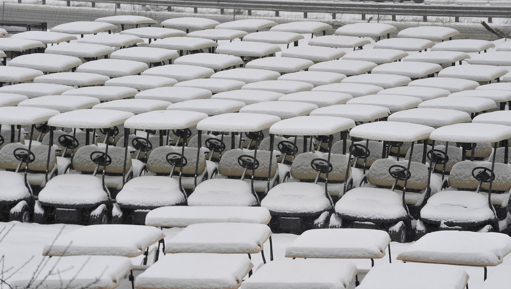 Description of . Golf carts, in a storage lot, are covered with snow in Holly, Mich., Thursday, Jan. 2, 2014.  (AP Photo/Detroit News,  Charles V. Tines)