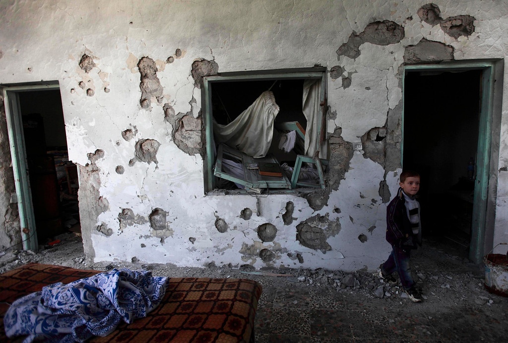 Description of . A child walks in a house damaged after heavy shelling by government forces in Sermeen near the northern city of Idlib February 28, 2012. REUTERS/Zohra Bensemra