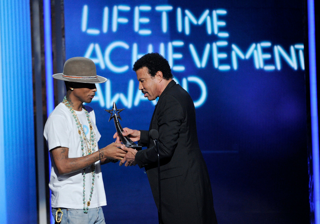 Description of . Pharrell Williams, left, presents the lifetime achievement award to Lionel Richie at the BET Awards at the Nokia Theatre on Sunday, June 29, 2014, in Los Angeles. (Photo by Chris Pizzello/Invision/AP)