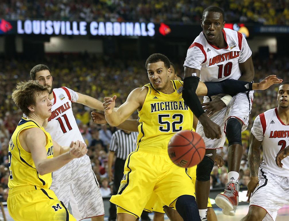Description of . Gorgui Dieng #10 and Luke Hancock #11 of the Louisville Cardinals fight for the loose ball in the second half against Spike Albrecht #2 and Jordan Morgan #52 of the Michigan Wolverines during the 2013 NCAA Men's Final Four Championship at the Georgia Dome on April 8, 2013 in Atlanta, Georgia.  (Photo by Streeter Lecka/Getty Images)