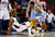 Charlotte Bobcats point guard Kemba Walker (L) falls to the ground as he takes a charge against Denver Nuggets shooting guard Andre Iguodala (R) during the second half of their NBA basketball game in Charlotte, North Carolina February 23, 2013. REUTERS/Chris Keane