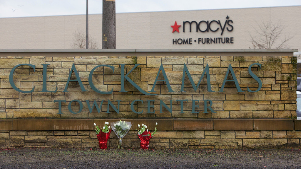 Description of . Flowers are left by a Clackamas Town Center shopping mall sign in Portland, Oregon, December 12, 2012. The masked gunman who opened fire in a crowded Oregon shopping mall, killing two people and wounding a third before taking his own life, appeared to have acted in a blind rampage with no known motive, authorities said on Wednesday. REUTERS/Steve Dipaola