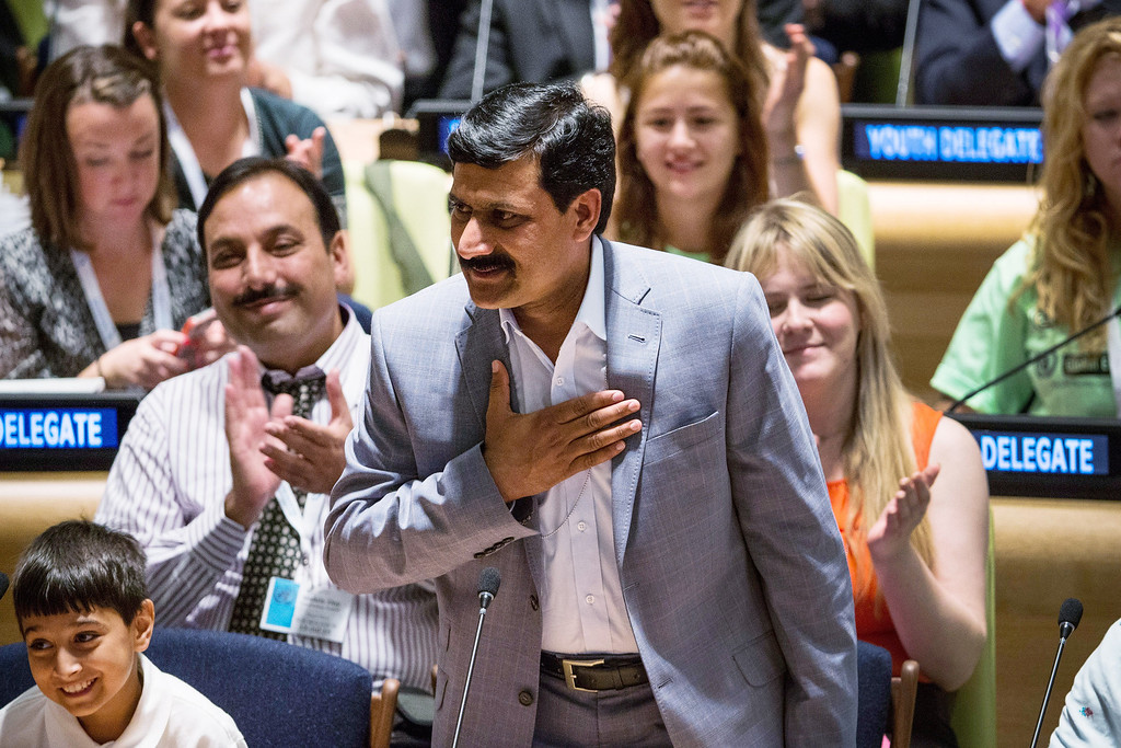 "Description of . NEW YORK, NY - JULY 12:  Ziauddin Yousafzai, father of Malala Yousafzai , the 16-year-old Pakistani advocate for girls education who was shot in the head by the Taliban, motions to the crowd before his daughter\'s speech at the United Nations (UN) Youth Assembly on July 12, 2013 in New York City. The United Nations declared July 12, ""Malala Day.\"" Yousafzai also celebrates her birthday today.  (Photo by Andrew Burton/Getty Images)"