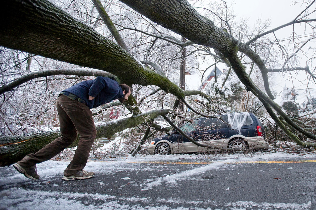 Description of . A man inspects an ice covered downed tree that took out an utility line and landed atop a minivan, after a winter storm Wednesday, Feb. 5, 2014, in Philadelphia.  (AP Photo/Matt Rourke)