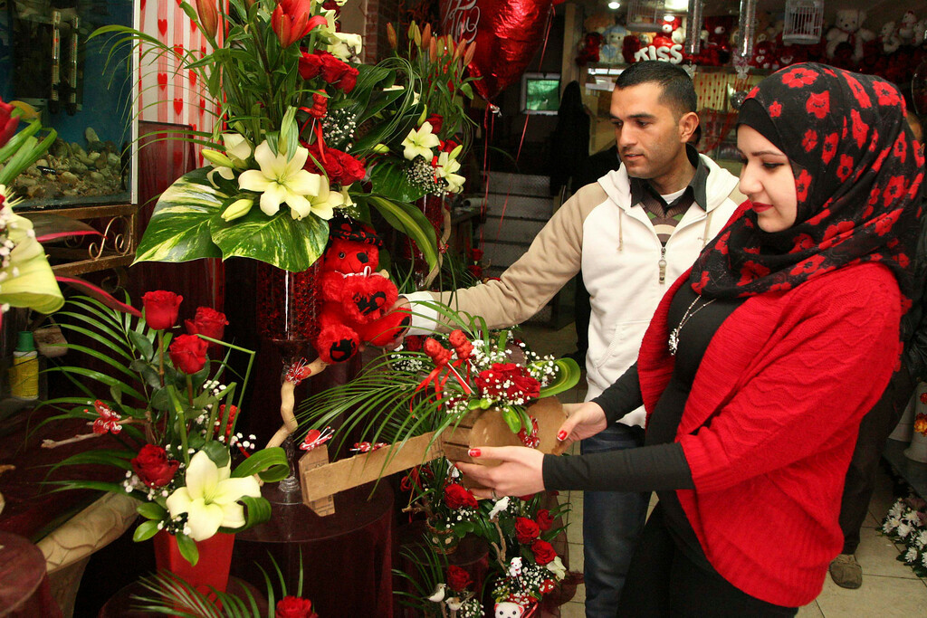 Description of . A vendor helps a woman to select her gift on Valentine's Day in Amman February 14, 2013. REUTERS/Majed Jaber