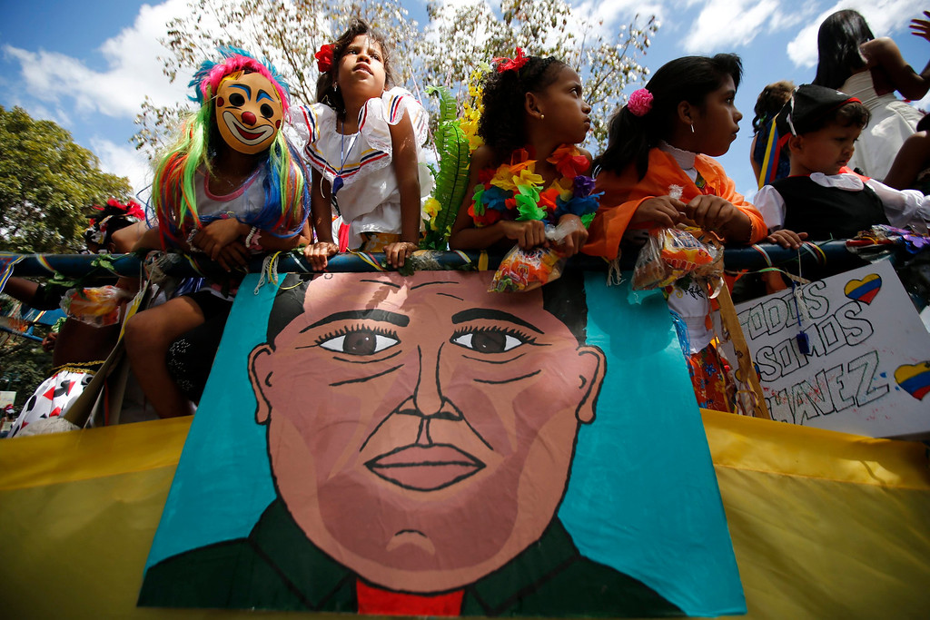 Description of . Children take part in a Carnival parade with an image depicting Venezuelan President Hugo Chavez in Caracas February 12, 2013. President Chavez is still in Cuba recovering from cancer surgery and has not been seen in public since December 8 last year. REUTERS/Jorge Silva