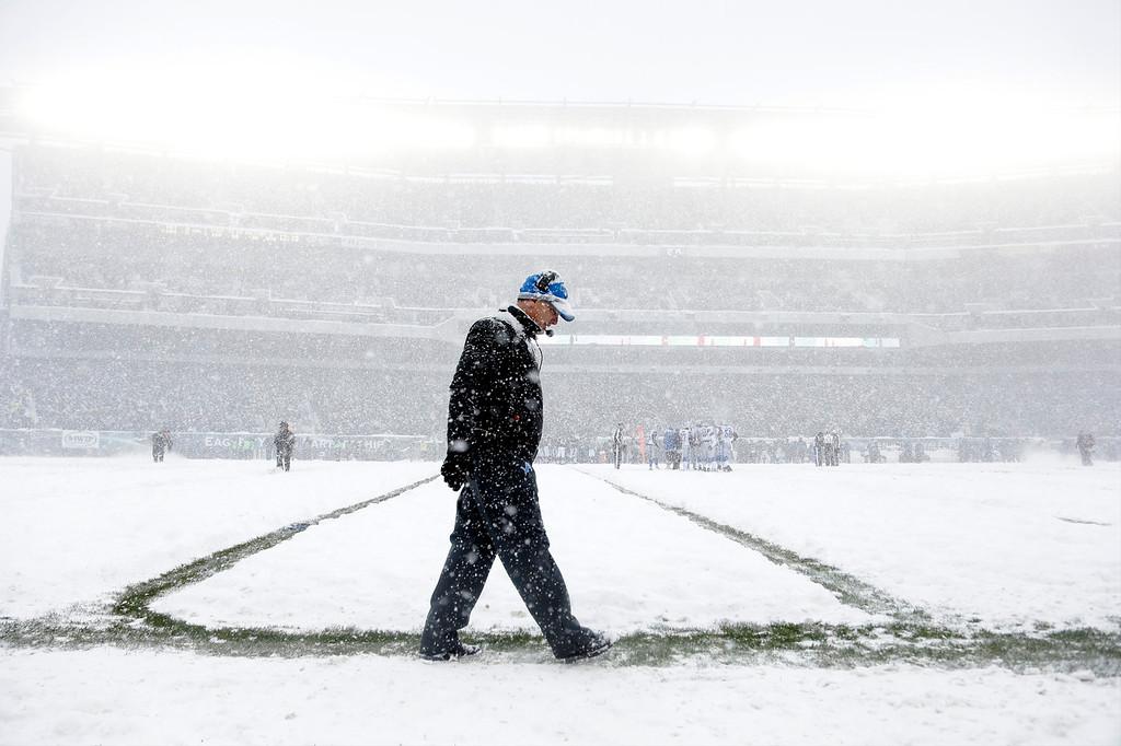 Description of . Detroit Lions head coach Jim Schwartz walks the sidelines as snow falls during the first half of an NFL football game against the Philadelphia Eagles, Sunday, Dec. 8, 2013, in Philadelphia. (AP Photo/Matt Rourke)