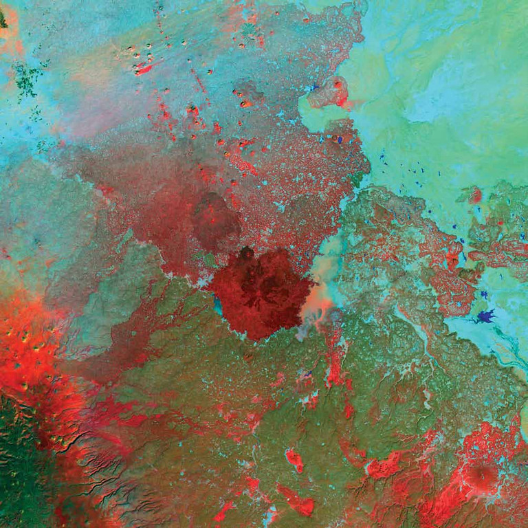 Description of . Syrian Desert, West Asia Between the cultivated lands along the eastern Mediterranean Sea and the fertile Euphrates River lies the Syrian Desert, covering parts of modern Syria, Jordan, Saudi Arabia, and Iraq. This Landsat 7 scene from 2000 centers on the southern end of the Syrian Desert�s As-Safa lava fields southeast of the city of Damascus. The image captures the hottest terrain in bright red, and these areas likely correspond to dark, barren, basaltic lava. Cooler terrain is bluish green, while pockets of lush vegetation in oases and towns are bright green. Cinder cones pockmark the northern fields, while bright blue pools of water appear throughout.   NASA