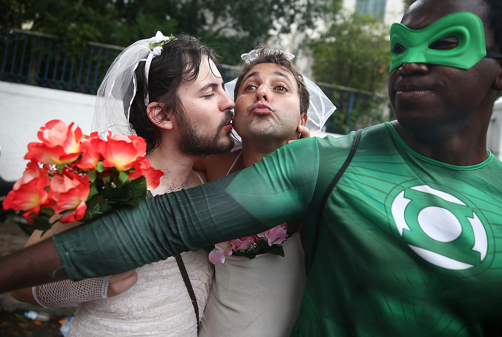 Description of . Revelers kiss while posing during the \'Ceu na Terra\' street carnival bloco on March 1, 2014 in Rio de Janeiro, Brazil. Carnival is the grandest holiday in Brazil, annually drawing millions in raucous celebrations.  (Photo by Mario Tama/Getty Images)