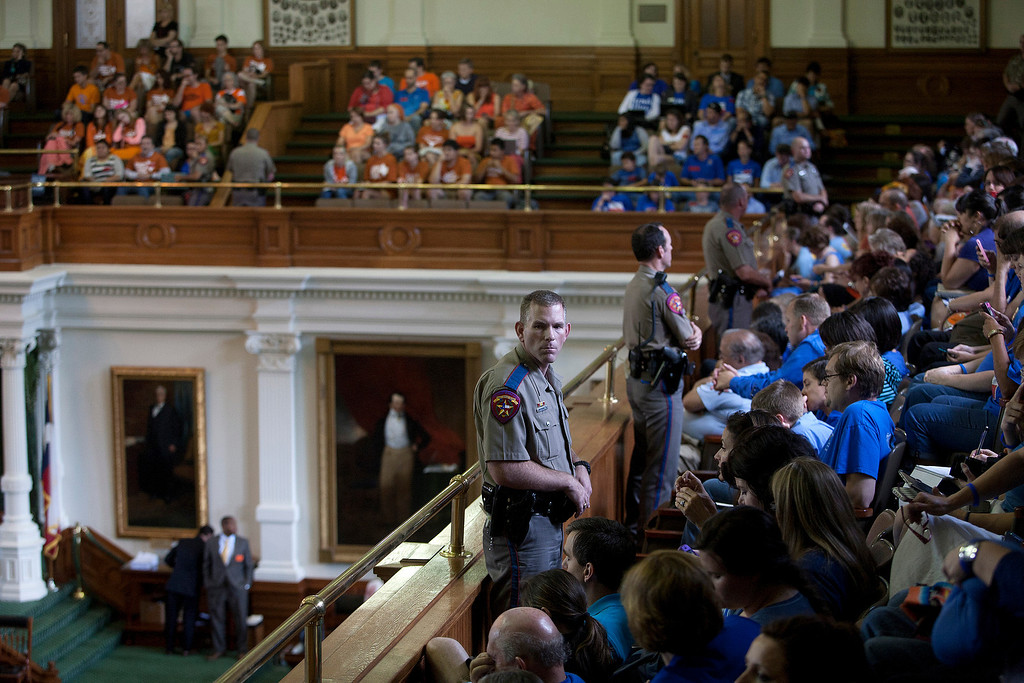 Description of . Over a dozen state troopers monitor the Senate Gallery of the State Capitol which is filled to capacity with supporters and opponents of abortion rights in Austin, Texas on Friday, July 12, 2013. The Texas Senate's leader, Lt. Gov. David Dewhurst, has scheduled a vote for Friday on the same restrictions on when, where and how women may obtain abortions in Texas that failed to become law after a Democratic filibuster and raucous protesters were able to run out the clock on an earlier special session. (AP Photo/Tamir Kalifa)