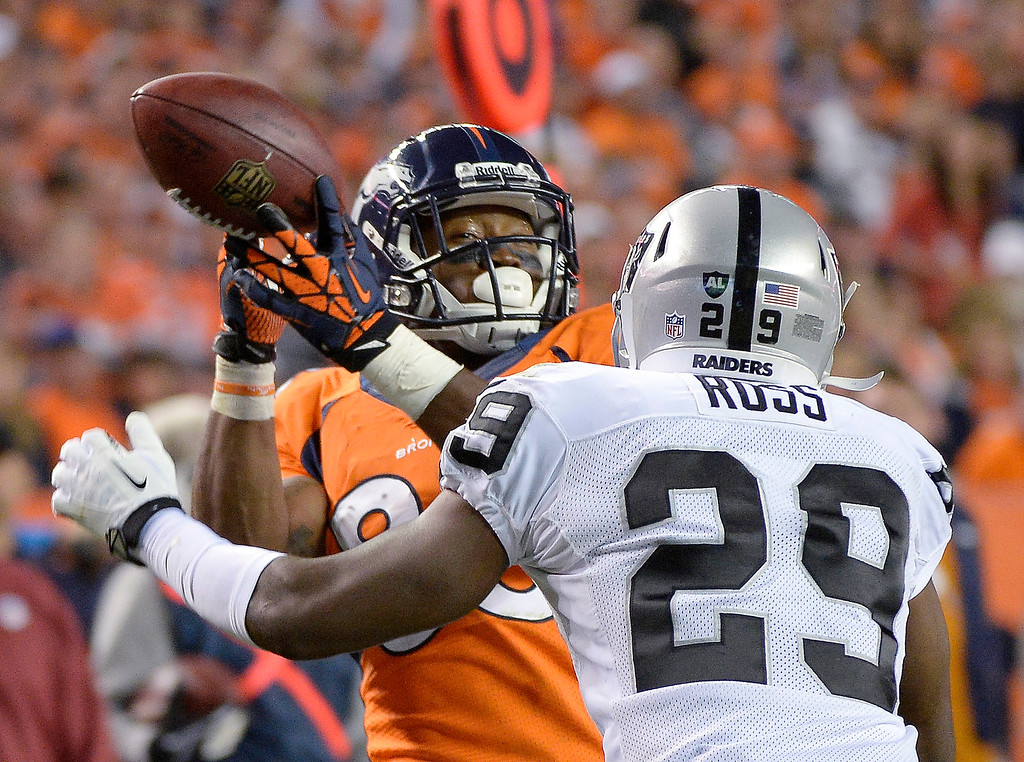 Description of . Denver Broncos wide receiver Demaryius Thomas (88) gets his finger tips on the ball but can't bring it in as Oakland Raiders cornerback Brandian Ross (29) prepares to hit him. The Denver Broncos took on the Oakland Raiders at Sports Authority Field at Mile High in Denver on September 23, 2013. (Photo by Joe Amon/The Denver Post)