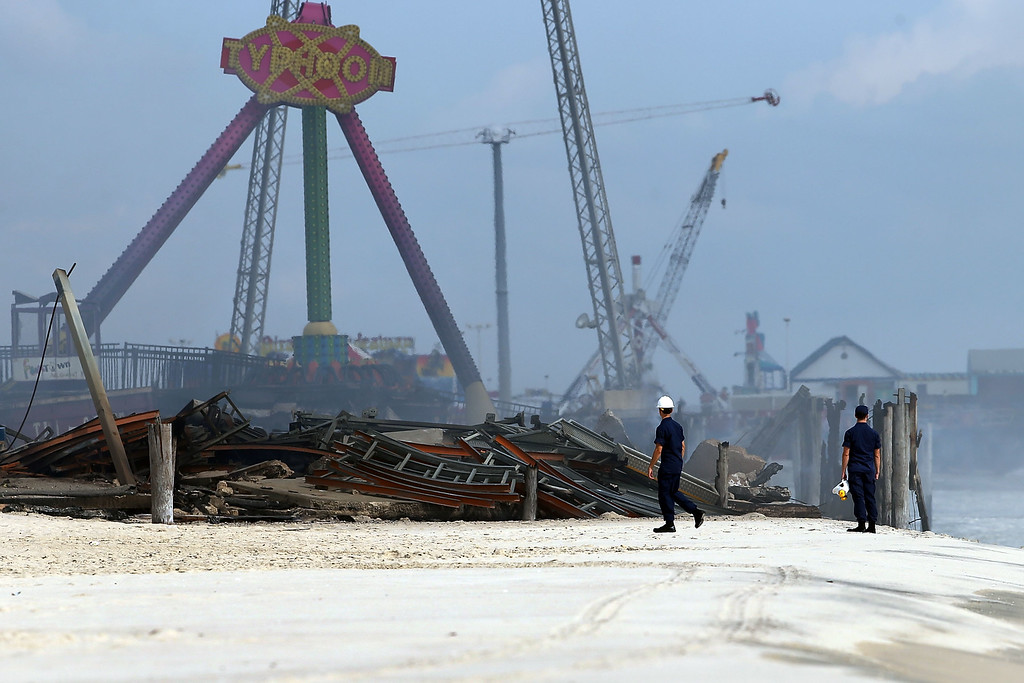 Description of . Two people walk near the destroyed remains of businesses along an iconic Jersey shore boardwalk on September 13, 2013 in Seaside Heights, New Jersey.  (Photo by Spencer Platt/Getty Images)