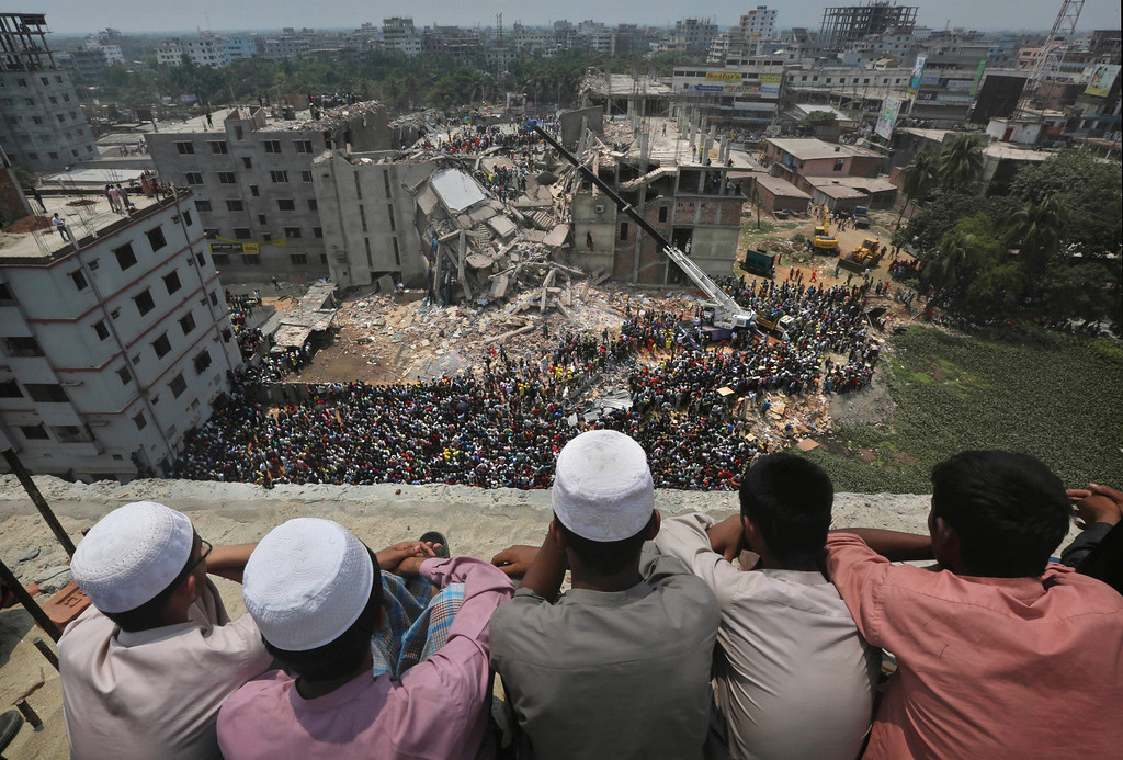 Description of . Bangladeshi boys watch the rescue operations from a rooftop at the site of a building that collapsed Wednesday in Savar, near Dhaka, Bangladesh, Thursday, April 25, 2013.  (AP Photo/Kevin Frayer)