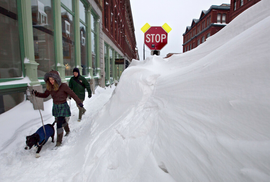 . A couple walks past a large snow drift in the Old Port section of Portland, Maine, Saturday, Feb. 9, 2013.  Officials are cautioning residents to stay off the roads in Maine, where Portland set an all-time snowfall record. (AP Photo/Robert F. Bukaty)