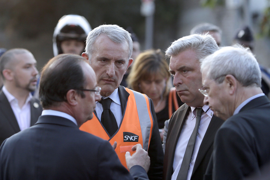Description of . French President Francois Hollande (L) talks with junior minister for Transport and Maritime Economy Frederic Cuvillier (2ndR) and national rail company SNCF head Guillaume Pepy (2ndL) during a visit on the site of an intercity train accident at the Bretigny-sur-Orge train station near Paris July 12, 2013. REUTERS/Kenzo Tribouillard/Pool