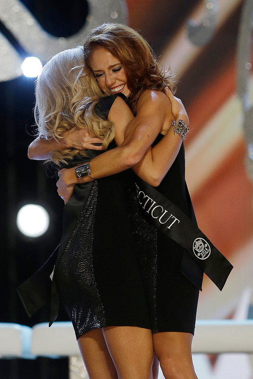 Description of . Miss Connecticut Kaitlyn Tarpey, right, hugs Miss Georgia Carly Mathis during the Miss America 2014 pageant, Sunday, Sept. 15, 2013, in Atlantic City, N.J. (AP Photo/Mel Evans)