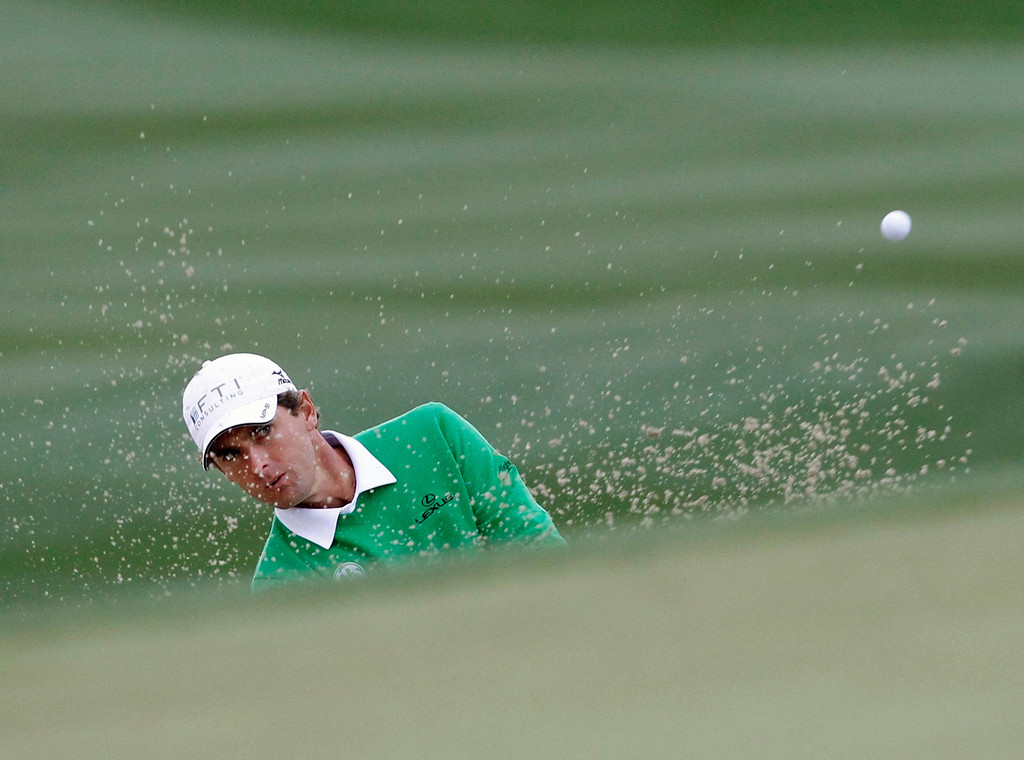 Description of . Charles Howell III of the U.S. hits from the sand onto the 13th green against Tiger Woods of the U.S. during the weather delayed first round of the WGC-Accenture Match Play Championship golf tournament in Marana, Arizona February 21, 2013. REUTERS/Matt Sullivan