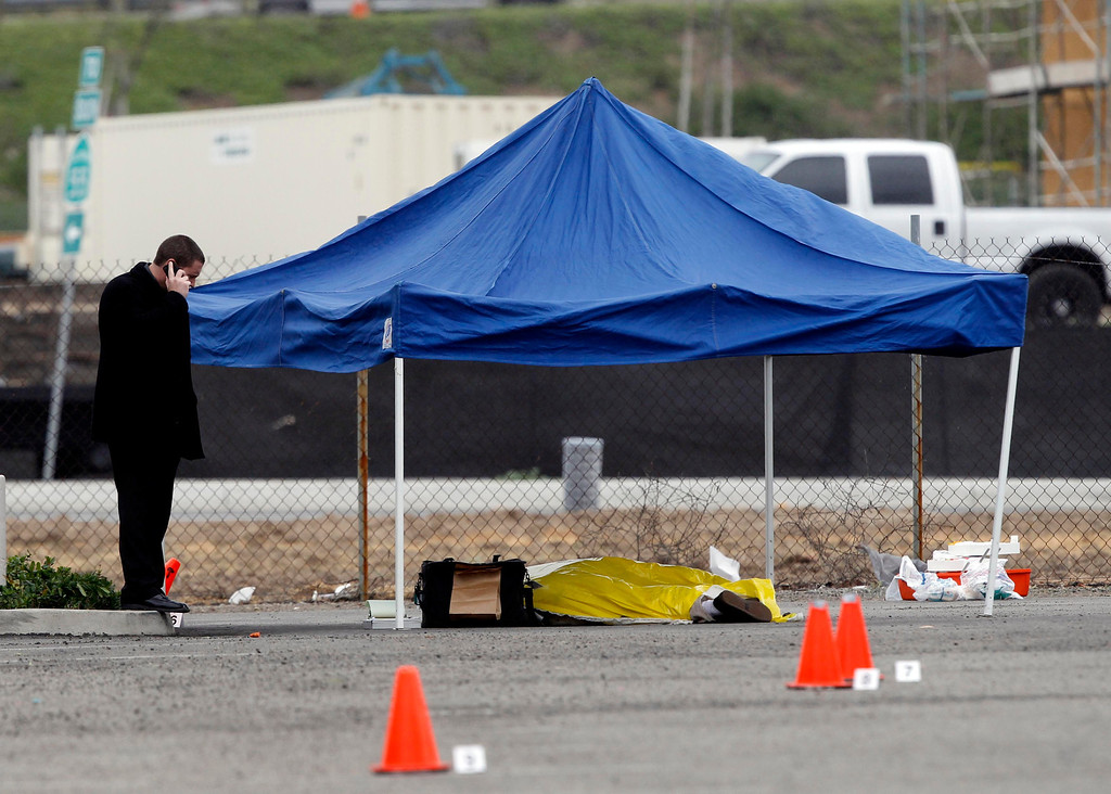 Description of . A police officer makes a call next to the body of a man in the parking lot of a computer store, after he was shot while returning to his vehicle, in Tustin, California, February 19, 2013. A gunman on a shooting rampage in southern California killed three people on Tuesday in an attack at a home and three carjackings, before killing himself with a shotgun as officers closed in, police said. REUTERS/Alex Gallardo
