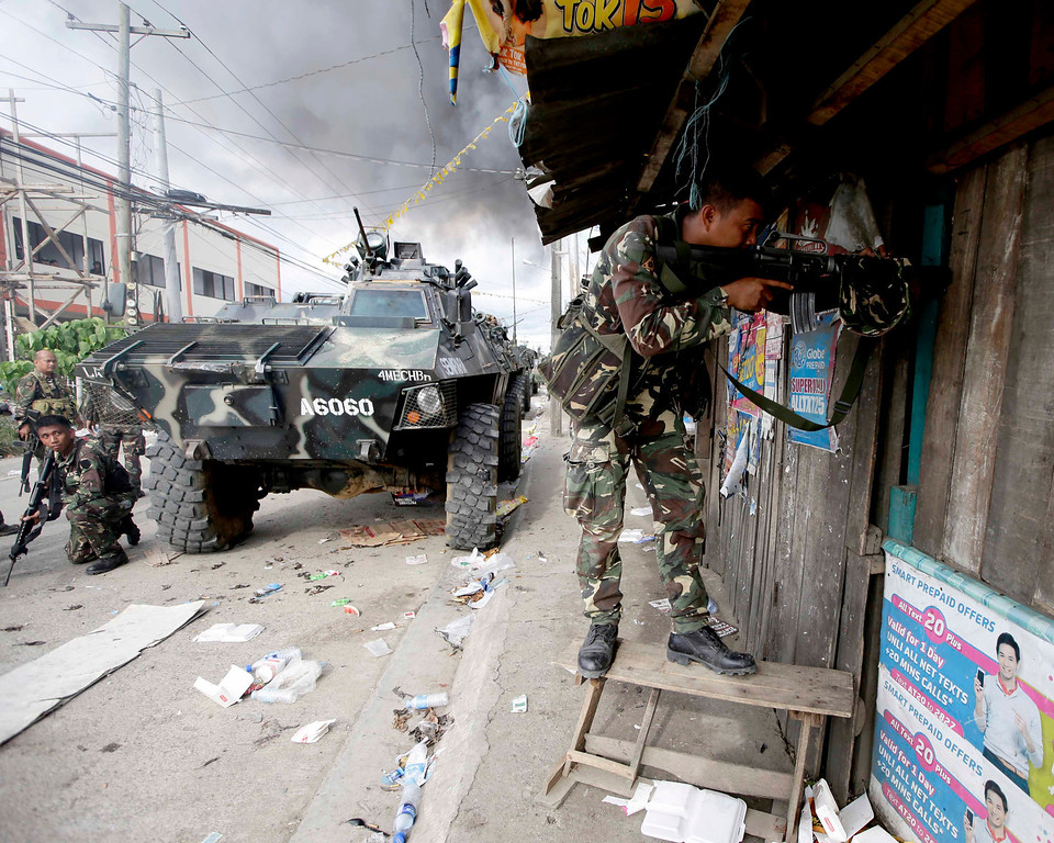 Description of . Government troopers continue their assault on Muslim rebels Thursday Sept. 12, 2013, in Zamboanga city in the southern Philippines.  (AP Photo/Bullit Marquez)