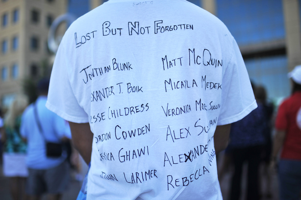 Description of . AURORA, CO. - July 20: Demetrius Adam of Aurora attends a day of remembrance wearing a t-shirt with the names of shooting victims at Aurora Municipal Center. Aurora, Colorado. July 20, 2013. People gathered outside the Aurora Municipal Center to mark the first anniversary of the deaths of 12 people and the injury of at least 70 others in a mass shooting that forever changed an entire community. (Photo By Hyoung Chang/The Denver Post)