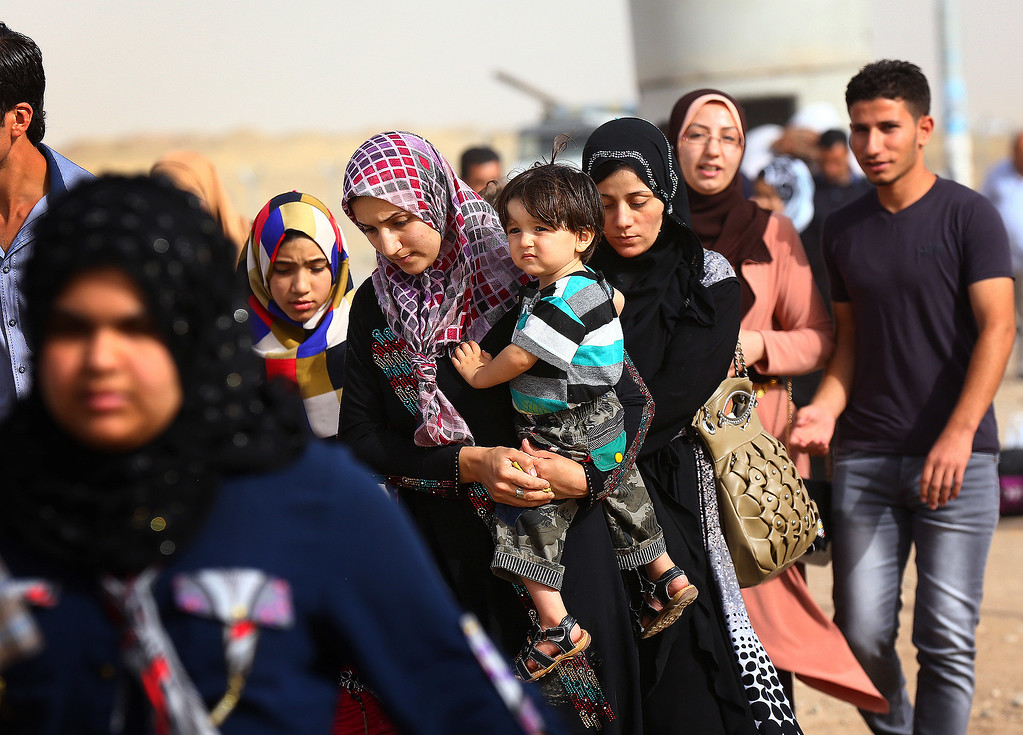 Description of . Refugees fleeing from Mosul head to the self-ruled northern Kurdish region in Irbil, Iraq, 350 kilometers (217 miles) north of Baghdad, Thursday, June 12, 2014. The Islamic State of Iraq and the Levant, the al-Qaida breakaway group, on Monday and Tuesday took over much of Mosul in Iraq and then swept into the city of Tikrit further south. An estimated half a million residents fled Mosul, the economically important city. (AP Photo)