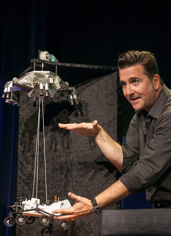 Description of . FILE - In this Thursday, Aug. 2, 2012 file photo, Adam Steltzner, Mars Science Laboratory's entry, descent and landing phase leader at JPL uses a scale model to explain the process during the Mission Engineering Overview news briefing at NASA's Jet Propulsion Laboratory in Pasadena, Calif. (AP Photo/Damian Dovarganes, File)