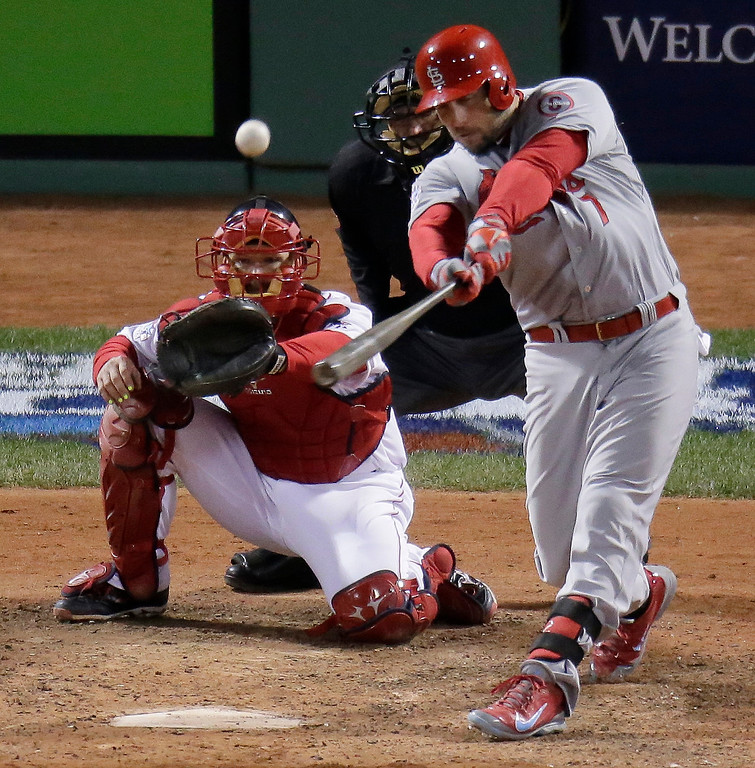 Description of . St. Louis Cardinals' Matt Holliday hits a home run in front of Boston Red Sox catcher David Ross during the ninth inning of Game 1 of baseball's World Series Wednesday, Oct. 23, 2013, in Boston. (AP Photo/Charlie Riedel)
