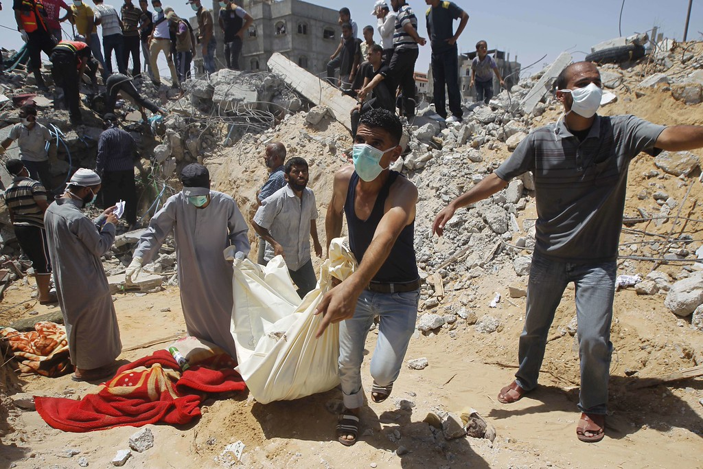 Description of . Palestinian rescue workers carry the body of a member of the Duheir family after removing it from under the rubble of their home which was destroyed in an Israeli air strike the previous day in Rafah in the southern Gaza Strip.  At least 54 people died in Israeli strikes across Gaza on July 30, including 16 killed when shells hit a UN school, sending the Palestinian toll from 23 days of fighting to more than 1,280. AFP PHOTO/ SAID  KHATIB/AFP/Getty Images