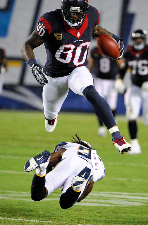 Description of . Houston Texans wide receiver Andre Johnson leaps over San Diego Chargers defensive back Richard Marshall during the first half of an NFL football game Monday, Sept. 9, 2013, in San Diego. (AP Photo/Denis Poroy)