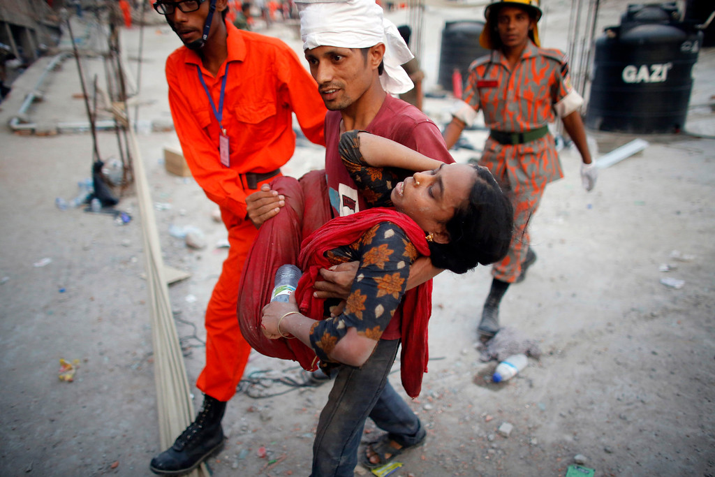 Description of . Rescue workers carry a garment worker who was trapped in the Rana Plaza building which collapsed, in Savar, 30 km (19 miles) outside Dhaka April 24, 2013. REUTERS/Andrew Biraj