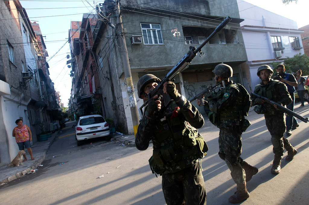 Description of . Army soldiers take position during an operation to occupy the Mare slum complex in Rio de Janeiro, Brazil, Saturday, April 5, 2014. More than 2,000 Brazilian Army soldiers moved into the Mare slum complex early Saturday in a bid to improve security and drive out the heavily armed drug gangs that have ruled the sprawling slum for decades. (AP Photo/Silvia Izquierdo)