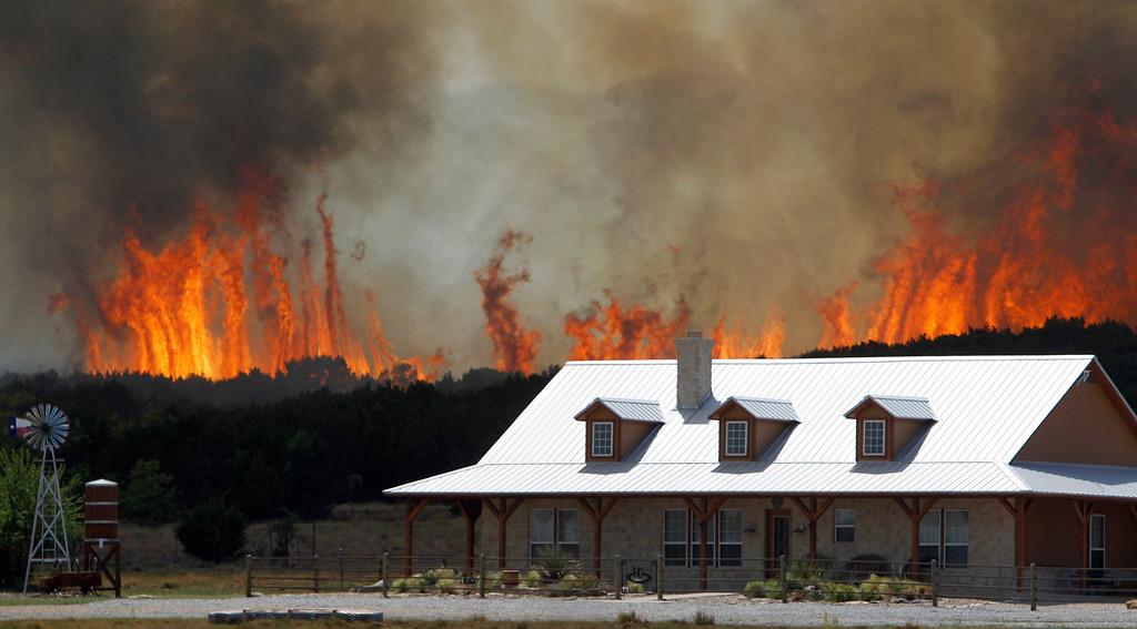 Description of . In this April 19, 2011 file photo, a wildfire threatens a house near Possum Kingdom, Texas.   (AP Photo/LM Otero)