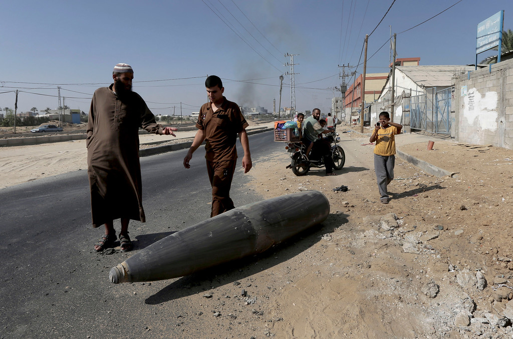 Description of . Palestinian onlookers and motorists pause to inspect a bomb from the Israeli military lying unexploded on the main road in Deir el-Balah in the central Gaza Strip, Friday, Aug. 1, 2014. (AP Photo/Adel Hana)
