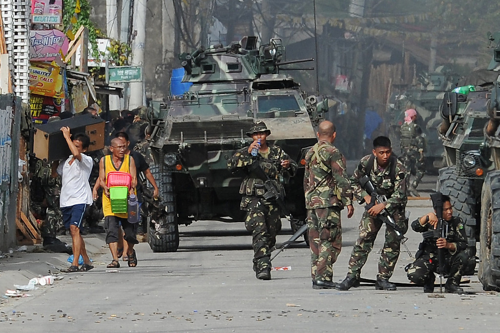 Description of . Residents (L) evacuate as soldiers take cover from sniper fire during a fire fight between government forces and Muslim rebels as stand-off entered its fourth day in Zamboanga City on the southern island of Mindanao on September 12, 2013.  AFP PHOTO/TED  ALJIBE/AFP/Getty Images
