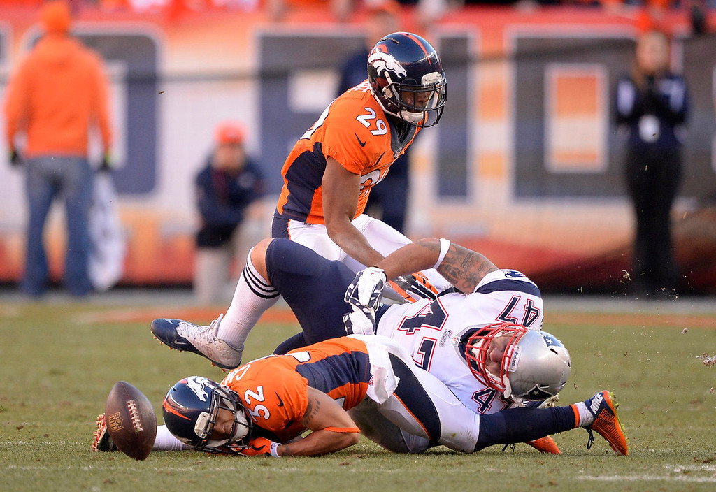 Description of . New England Patriots tight end Michael Hoomanawanui (47) lands on Denver Broncos cornerback Tony Carter (32) after Carter nearly intercepted quarterback Tom Brady (12). The Denver Broncos vs. The New England Patriots in an AFC Championship game  at Sports Authority Field at Mile High in Denver on January 19, 2014. (Photo by John Leyba/The Denver Post)